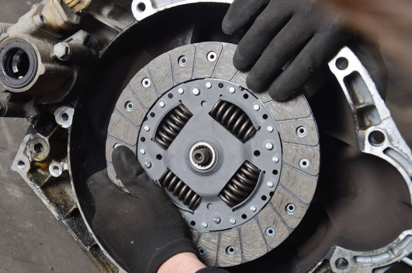 mechanic wearing black goves replacing clutch
