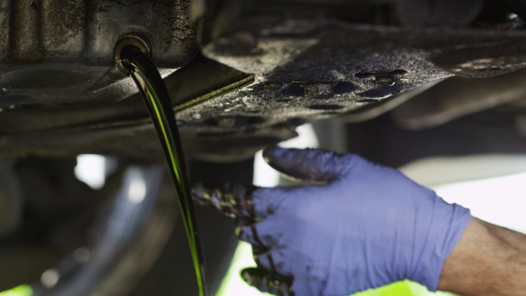 Mechanic draining oil from a car